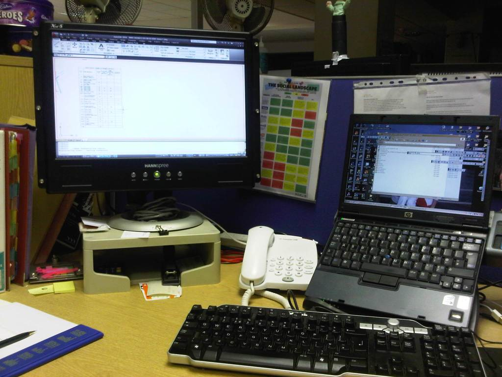 A typical cubical desk with a laptop, telephone and monitor. It is pretty messy.