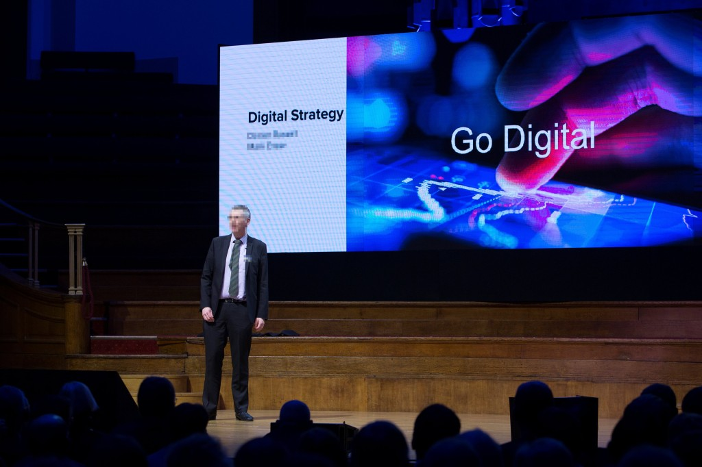 "An executive addressing an audience. The screen behind him contains a message to ""Go Digital"""